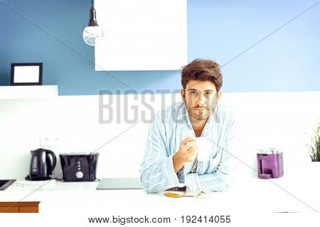Portrait of young ill man holding coffee mug while leaning on kitchen counter