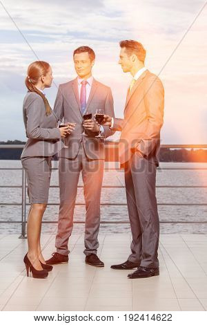 Full length of businesspeople with wineglasses standing on terrace