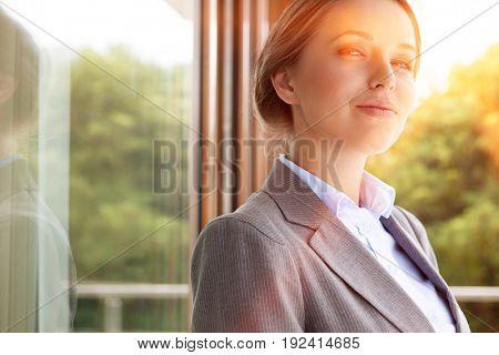 Portrait of confident businesswoman by glass door