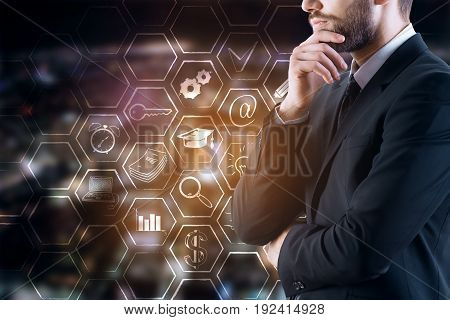 Side view of thoughtful young businessman in suit standing on blurry night city background with business icons in cells. Tech concept. Double exposure