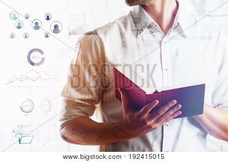Businessman in white shirt holding open book on bright background with business graphs. Financial growth concept. Double exposure