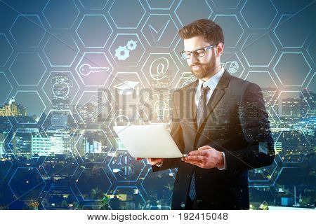 Young businessman in suit holding laptop on night city background with business icons in cells. Work concept. Double exposure