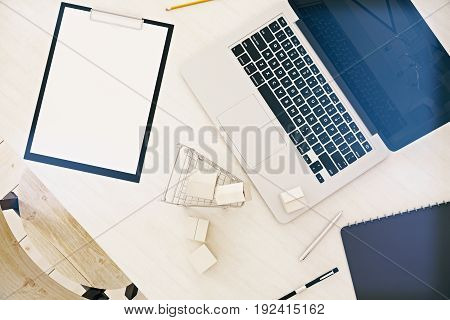 Top view of office desktop with empty laptop small shopping card model and blank clipboard. Announcement concept. Mock up 3D Rendering
