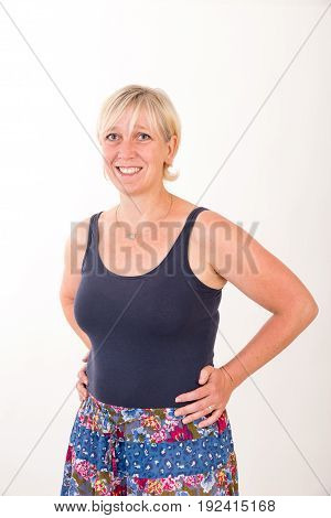 portrait of a attractive blond haired mid aged european woman wearing blue top and colored skirt.