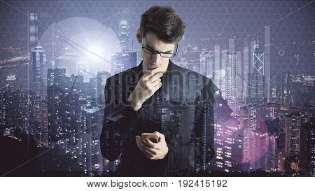 Businessman using smartphone on bright night city background with business charts. Technology concept. Double exposure