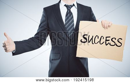Man holding carboard success banner and showing thumbs up on grey background