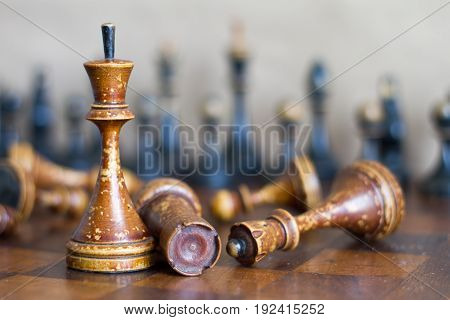 Ancient wooden chess pieces on an old chessboard.