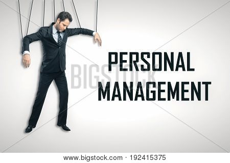 Businessman puppet on light background with text. Personnel management concept