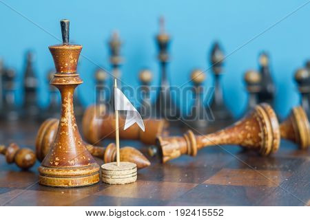 Ancient wooden chess pieces on an old chessboard. With the white flag of surrender. On a blue background.