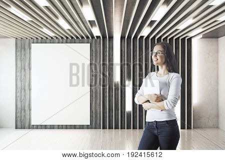 Cheerful young businesswoman standing in unfurnished hipster interior with empty poster on wall. Mock up 3D Rendering
