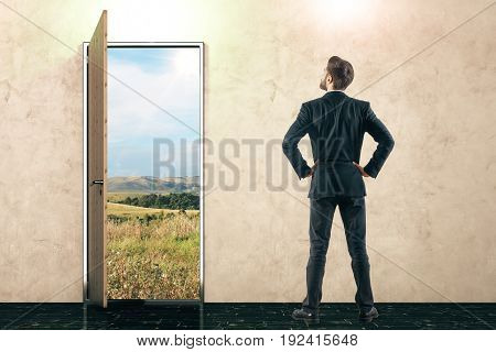 Open door with landscape view and thoughtful businessman in concrete interior. Success concept