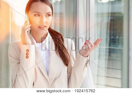 Businesswoman gesturing while answering cell phone against glass door