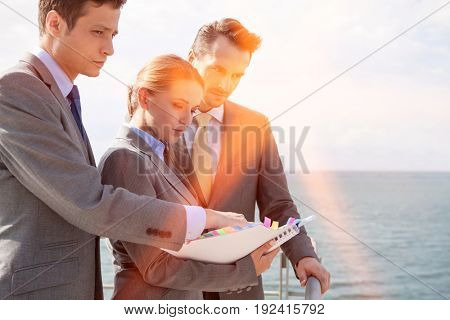 Businessteam with book standing on terrace against sky