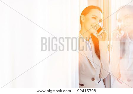 Happy businesswoman answering cell phone in office