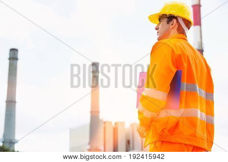 Back view of male architect with clipboard standing at site