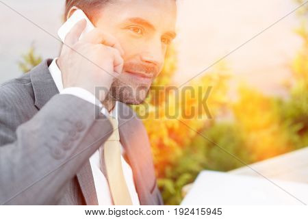 Businessman answering cell phone outdoors