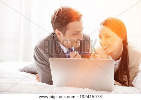 Playful business couple with laptop in hotel room