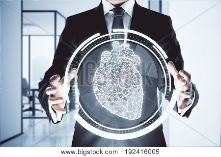 Businessman holding abstract digital circle with polygonal heart in interior. Cardiology concept. 3D Rendering