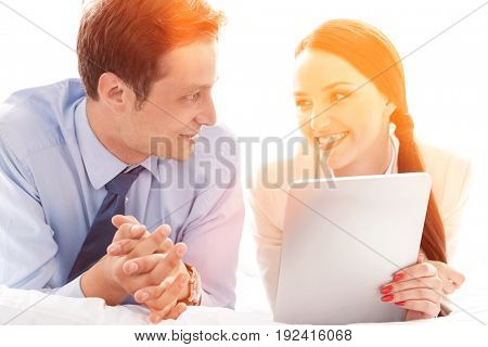 Happy business couple with digital tablet looking at each other in hotel