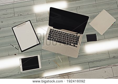 Top view of empty laptop tablet and paperwork placed on glass table in modern interior with wooden floor. Mock up 3D Rendering