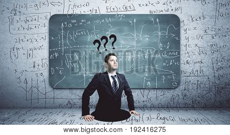 Businessman with questions standing in abstract hole. Concrete wall with mathematical formulas on chalkboard in the background. Knowledge concept
