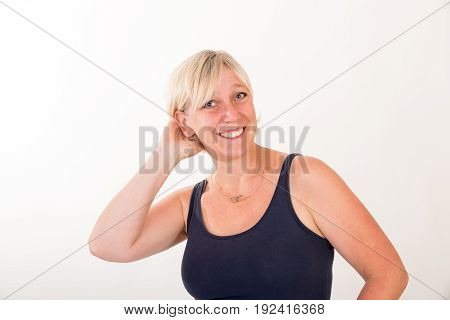 portrait of a attractive blond haired mid aged european woman wearing blue tank top showin happy face - half body - studio shot on white background.