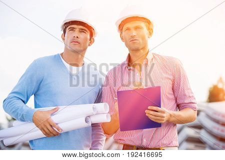 Architects with blueprint and clipboard standing at site