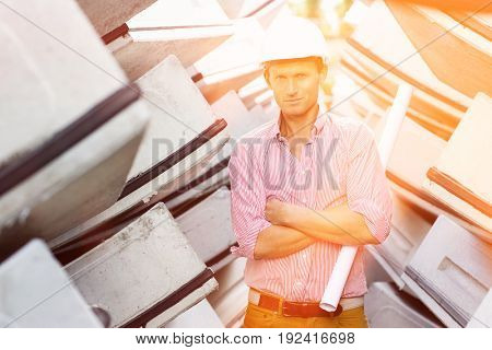 Portrait of male architect holding rolled up blueprint at construction site