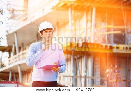 Thoughtful architect with clipboard and pen standing at site