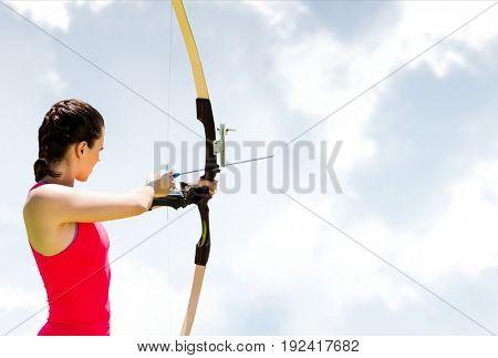 Digital composite of Woman archery against sky