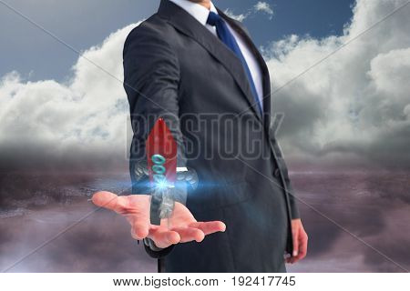 Digital composite of Business man holding a rocket on his hand against sky background