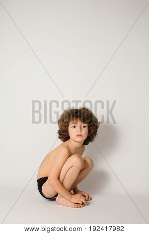 Little curly-haired boy in shorts sitting on his haunches and looking at the camera. Gray background.