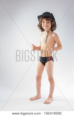 Little curly-haired cowboy hat and bathing suit stands laughing and looking at the camera. Gray background.