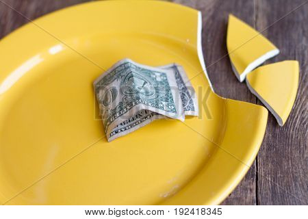 Broken plate yellow and one dollar old paper on wooden background.