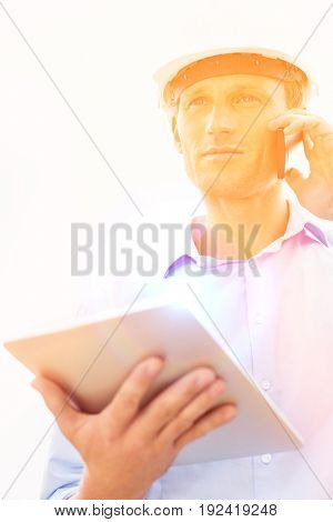Low angle view of male architect with digital tablet using cell phone against sky