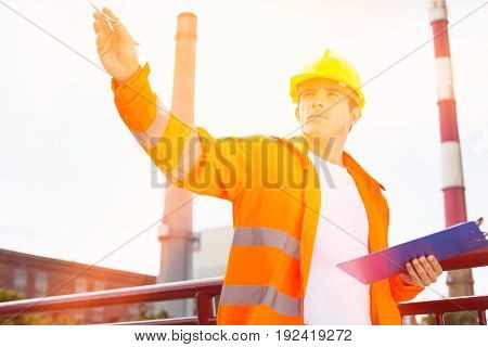 Male architect with clipboard at industry