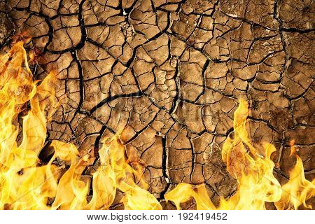 Cracked dry soil of earth texture with fire flames. Global warming concept.