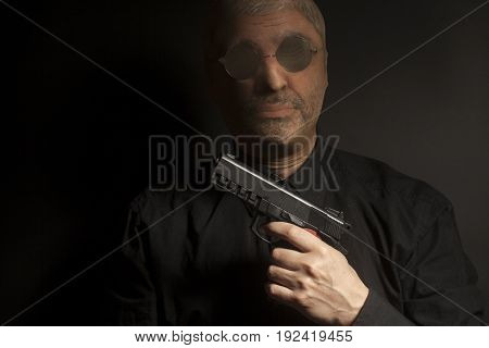criminal bandit man wearing a stocking mask holds a gun in his hand on black background