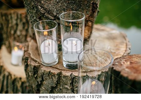 Candles in decorated goblets. Wedding decorations in rustic style. Outing ceremony. Wedding in nature. Selective focus.