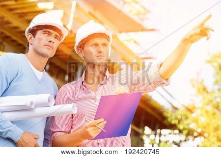 Male architects with blueprint and clipboard working at site