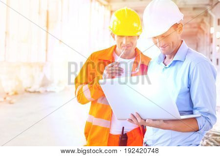 Male architects using laptop at construction site