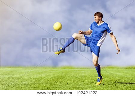 The soccer player is playing soccer on the green grass playing field in blue sports clothing on sky background shooting the yellow football ball.