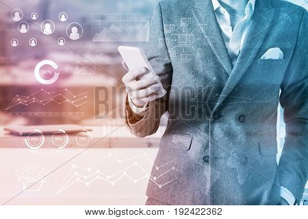 Close up of young businessman using smartphone in modern office with digital business pattern. Communication concept. Double exposure