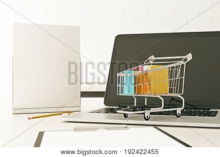 Close up of office desktop with empty laptop screen blank poster and tiny shopping cart. Advertisement concept. Mock up 3D Rendering