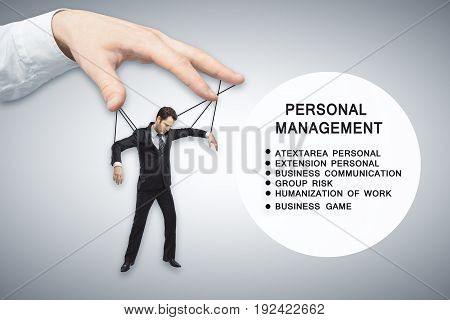 Hand manipulating businessman puppet on light background with text
