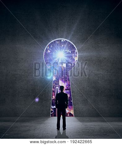 Back view of young businessman standing in concrete interior with keyhole opening and illuminated night city view. Success concept. 3D Rendering