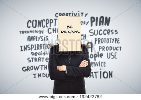 Businessman with cardboard box on head. Light backgroud with inspirational text. Be original concept