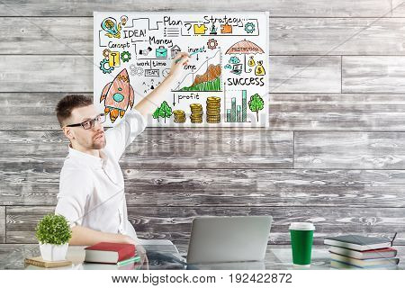 Handsome businessman pointing at whiteboard with business doodle while sitting at desk with items. Wooden background. Presentation concept