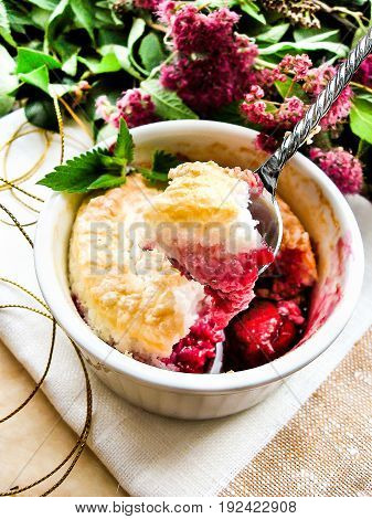 Homemade souffle or pudding with fresh cherry and coconut in a ramekin, selective focus