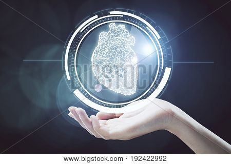Hand holding abstract digital circle with polygonal heart inside. Innovative technologies concept. 3D Rendering